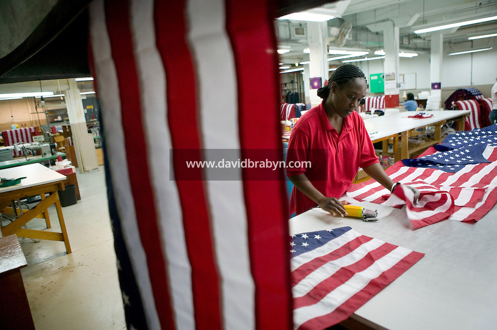 21 June 2005 - Oaks, PA - Shandell Boyd uses electric sliders to separate American flags coming down from the workshop above at the Annin & Co. flag manufacturing plant in Oaks, PA. Photo Credit: David Brabyn