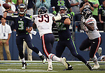 Seattle Seahawks' quarterback Russell Wilson (5) looks to pass while being pressured from Chicago Bears' defensive end Lamarr Houston (99) in a pre-season game at CenturyLink Field in Seattle, Washington on August 12, 2014.  Attempting to block Houston is tight end Luke Wilson (82). Seattle beat Chicago 34-6. Wilson completed 15 of 20 passes for 202 yards passed for two touchdowns and ran for another in the win. © 2014.  Jim Bryant Photo. ALL RIGHTS RESERVED.