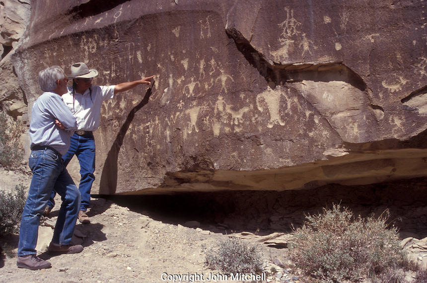 Ute Indian guide explaining Anasazi petroglyphs to a tourist in Ute Mountain Tribal Park near Mesa Verde National Park, Colorado, USA