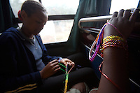 "young  actresses of the voices of youth theater company, make neckelesses and rist bands out of colored plastic wire on their bus during the tour  of the ""voices of youth"" theater project in Harar on the way to Babile, Ethiopia on Saturday August 12 2006..Voices of Youth, a play about the challenges faced by Ethiopian children: HIV, domestic violence, homelessness, poverty, drug addiction, and sexual abuse, a potpourri of deprivation, written by the children themselves. Their parents died of AIDS, and many are themselves infected. Quite a few have firsthand experience of the themes they are portraying. They are staging their own lives. .Ethiopia is one of the countries most affected by HIV/AIDS. Of its population of 77 million, three million are HIV-positive, according to government statistics. Every day sees 1,000 new infections. A million children under 14 have lost one or both parents to AIDS, and 200,000 children are living with AIDS. That makes Ethiopia the country with the most HIV-positive children."