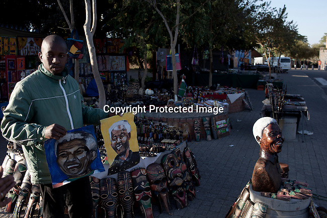 SOWETO, SOUTH AFRICA : An unidentified man sells Nelson Mandela  souvenirs next to Hector Pieterson museum in Soweto, South Africa. (Photo by Per-Anders Pettersson)