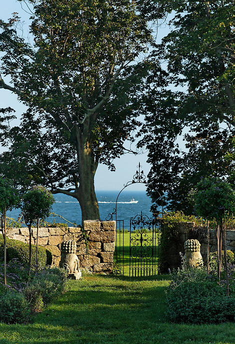 Chinese lions frame a wrought iron gate and view of the ocean with fishing boat . Harkness, a  CT State Park.
