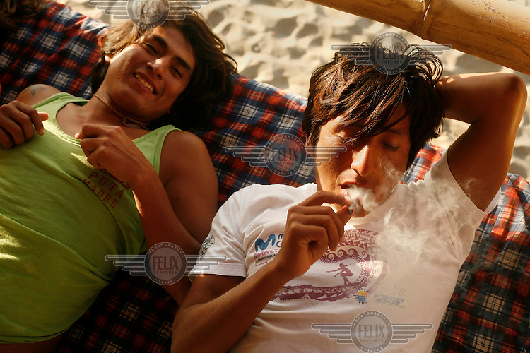 Two young men smoke cannabis on the beach. Mancora was once a quiet fishing village but due to its world class surf break it has become a magnet for surfers from around the world while many of the younger villagers have adopted a surfing lifestyle.