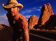 A man with tattoos and a cowboy hat leans into the camera while taking a break from riding his motorcyle in the Arizona desert.
