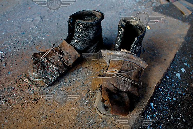 In absence of safety equipment a worker using oxy-acetylene gases at a steel recycling and re-rolling mill has attached a pair of thick gloves to his boots in order to add some minisculet measure of extra protection.