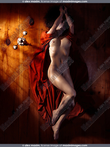Beautiful nude woman with tied hands in red kimono spread around on the floor lying in dim candle light
