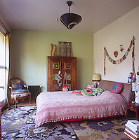 A bedroom with one white and one green painted wall and a purple floral pattern rug. A double bed has an upholstered headboard and a pink cover. A freestanding wooden cupboard stands against one wall.