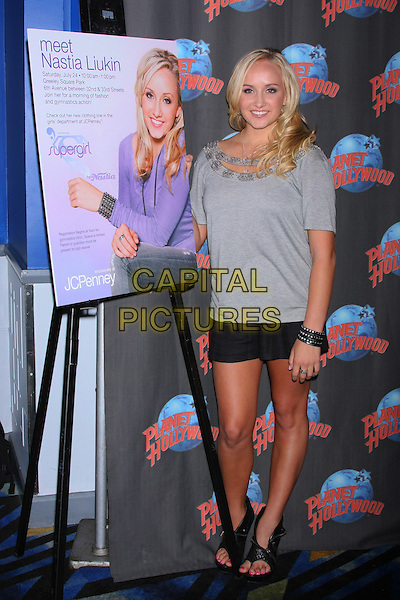 NASTIA LIUKIN.Gold Medal winning gymnast launches her clothing line, Supergirl by Nastia at Planet Hollywood Times Square during a meet-and-greet luncheon with local Girl Scouts. New York, NY, USA, .23rd July 2010..full length grey gray top poster black skirt cuff bracelet  shorts thong shoes sandals open toe .CAP/LNC/TOM.©TOM/LNC/Capital Pictures.