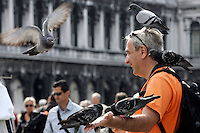 Un turista gioca con i piccioni in Piazza San Marco a Venezia.<br /> A tourist plays with pigeons in front of the Patriarchal Cathedral Basilica of St. Mark in Venice.<br /> UPDATE IMAGES PRESS/Riccardo De Luca