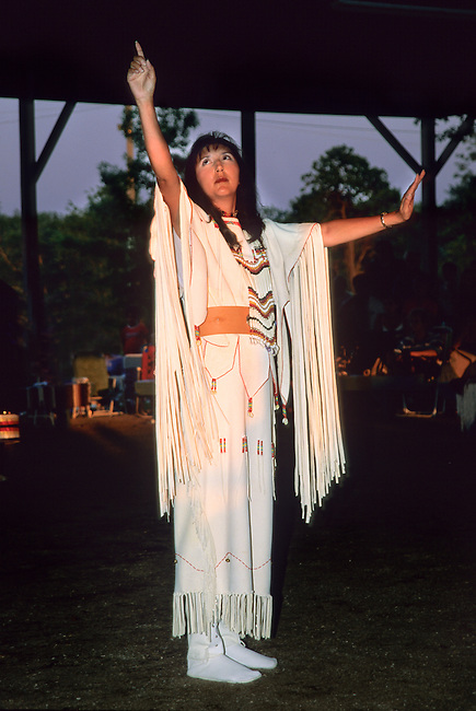 Woman dressed in traditional brain tanned fringed dress demonstrates Native American sign language during an opening prayer at the annual Miami Potawatomi Pow Wow, Oklahoma