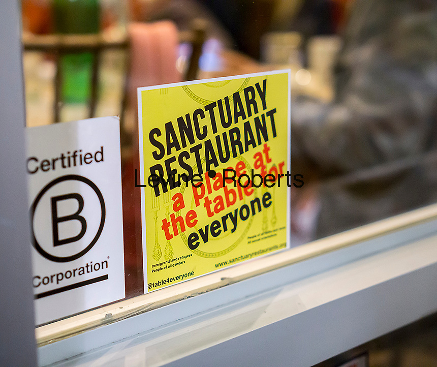"A sign in the window of the Green Table restaurant in Chelsea in New York announces that it is a ""sanctuary restaurant"" protecting immigrant rights, seen on Thursday, January 26, 2017. The ""sanctuary restaurant"" movement is an effort to protect workers in the restaurant industry which employees many immigrants. (© Richard B. Levine)"