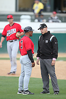 Umpire John Bostwick talks with first base coach Tommy Cruz of the High Desert Mavericks during game with the Rancho Cucamonga Quakes  at The Epicenter in Rancho Cucamonga,California on May 8, 2011. Photo by Larry Goren/Four Seam Images