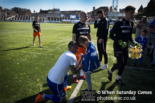 The home team's veteran striker Derek Lyle signing an autograph for a young fans on the pitch at Palmerston Park, Dumfries before Queen of the South hosted Dundee United in a Scottish Championship fixture. The home has played at the same ground since its formation in 1919. Queens won the match 3-0 watched by a crowd of 1,531 spectators.