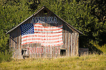 Wooden barn with US flag painted on it: America, Proud of It, Iowa.