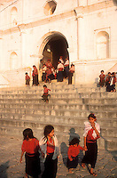 Children leave a church service in San Antonio Palopo, Guatemala. Both men and women still wear traje. Women wear backstrap loomed red striped huipiles, red head ribbons, and blue skirts. Men dress in similar striped shirts and pants with a small woolen blanket called a rodillera around the hips. .Photograph by Peter E. Randall