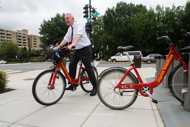 After touring the Metro Police Department's harbor patrol facilities Councilmember Tommy Wells hops on a Capital Bike Share bike to get back to his office.