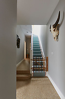 The hallway is decorated in a soft grey with sisal carpeting. A rustic style miniature gate stops access to the flight of stairs beyond.