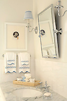 Accents of blue and white are used in the gingham lampshades of the wall lights and towels in the boy's bathroom