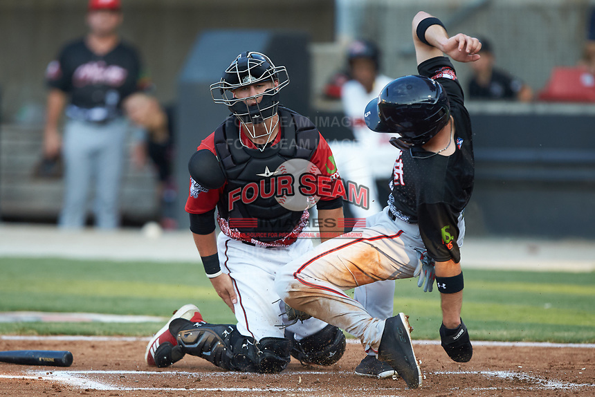 Carter Kieboom (4) of the Potomac Nationals of the North Division slides across home plate ahead of the tag by South Division catcher Max McDowell (4) of the Carolina Mudcats at Five County Stadium on June 19, 2018 in Zebulon, North Carolina. The South All-Stars defeated the North All-Stars 7-6.  (Brian Westerholt/Four Seam Images)