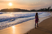 Photo of Mirissa Beach, tourist on Mirissa Beach at sunset, South Coast of Sri Lanka, Southern Province, Asia. This is a photo of a tourist walking on Mirissa Beach at sunset, Sri Lanka, Asia. Mirissa Beach, a palm tree lined beach on the South Coast of Sri Lanka is one of the most popular tourist beaches and is host to many a beautiful sunset.