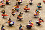 Tsechu Dancers, Paro Dzong, Bhutan<br /> Cloaked in long, colorful costumes, a troupe of Bhutanese dancers resemble spinning tops as they celebrate at a Buddhist festival or tsechu in the courtyard of Paro Dzong.