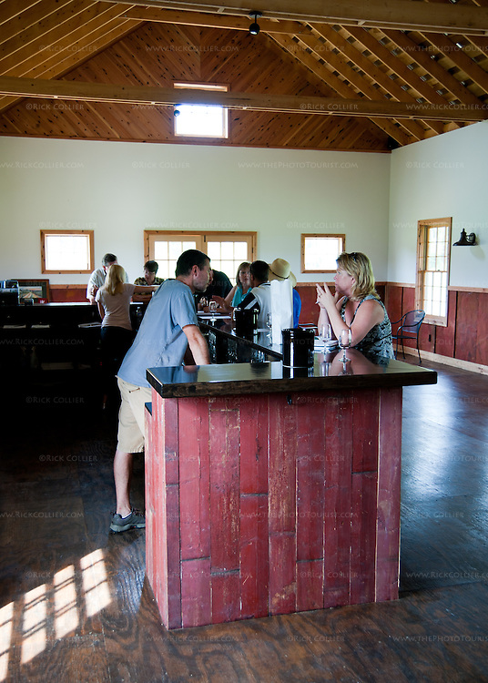 Nancy chats with the owner over the tasting bar at Hume Vineyards.  The bar was made from old barn wood from the barn that once stood on this site.