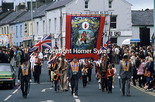 Orangeman Day parade. Protestant July 4th parade Red Hand Commandos Killycoogan Rising Sons banner. Featuring William of Orange.