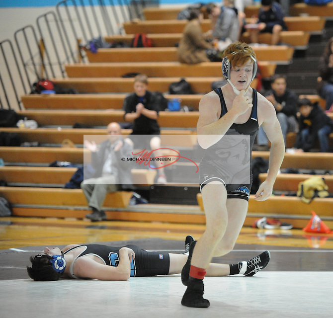 Eagle River's Grant Burningham  jumps up following his pin of Chugiak's Luke Momblow at Chugiak High School. Photo by Michael Dinneen for the Star.
