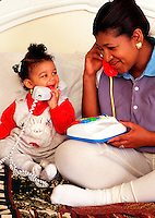 Indian-Asian mother and daughter play together with a telephone