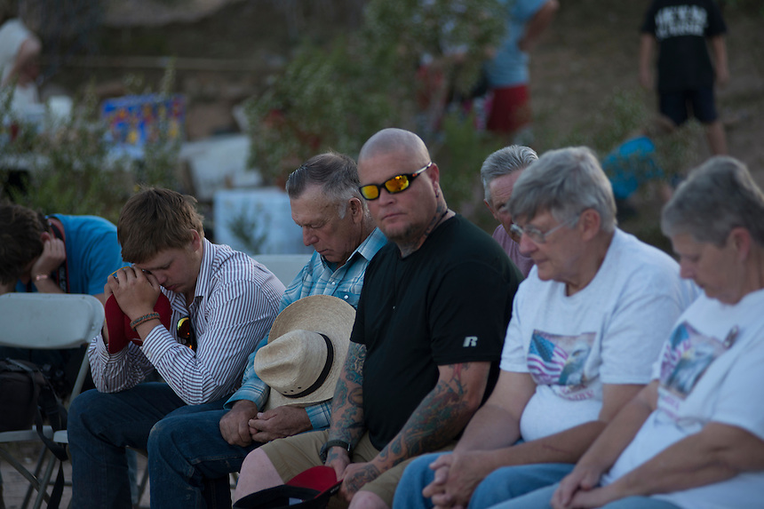 Cliven Bundy, one of his 14 children (L), his body guard (R) at an evening prayer gathering and cookout provided by Bundy for his supporters, near the Cliven Bundy ranch in Bunkerville, Nevada.<br /> <br /> Supporters of Bundy came from all over the country to defend against what they believe is government overreach.<br /> The Bundy standoff is a 20-year legal dispute between the United States Bureau of Land Management (BLM) and cattle rancher Cliven Bundy, over unpaid grazing fees, that recently provoked an armed confrontation between protesters and law enforcement.