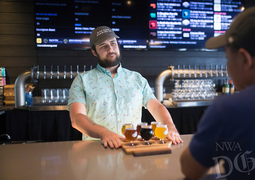 NWA Democrat-Gazette/CHARLIE KAIJO Bartender John Jolly (center) serves a flight of beer to Sonephet Manivong of Grand Island, Neb. (right), Thursday, August 8, 2019 at the Bike Rack Brewing in Bentonville.<br /> <br /> Bike Rack Brewing is distributing into Little Rock now.