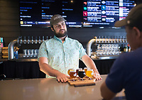NWA Democrat-Gazette/CHARLIE KAIJO Bartender John Jolly (center) serves a flight of beer to Sonephet Manivong of Grand Island, Neb. (right), Thursday, August 8, 2019 at the Bike Rack Brewing in Bentonville.<br /> <br /> Bike Rack Brewing is distributing into Little Rock now.
