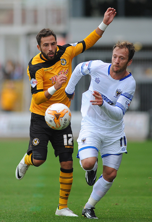 Newport County's Robbie Willmott vies for possession with AFC Wimbledon's Sean Rigg<br /> <br /> Photographer Kevin Barnes/CameraSport<br /> <br /> Football - The Football League Sky Bet League Two - Newport County AFC v AFC Wimbledon - Saturday 27th September 2014 - Rodney Parade - Newport<br /> <br /> &copy; CameraSport - 43 Linden Ave. Countesthorpe. Leicester. England. LE8 5PG - Tel: +44 (0) 116 277 4147 - admin@camerasport.com - www.camerasport.com