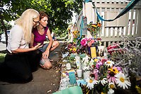 Elisa Byler (cq, left) and Rebecca Carlson (cq) look at flowers and notes during a memorial for Robin Williams (cq) at the home where the hit television show Mork and Mindy took place in Boulder, Colorado, Wednesday, August 13, 2014. Williams, who rose to fame starring in Mork and Mindy, died at the age of 63 from an apparent suicide. <br /> <br /> Photo by Matt Nager