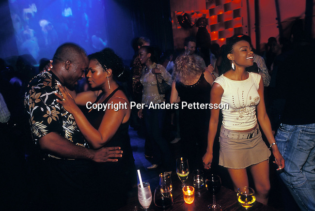 dippnig00161 People Nightlife JOHANNESBURG, SOUTH AFRICA -  FEBRUARY 14: Unidentified up market black people enjoying themselves at Kilimanjaro, a trendy club, on February 14, 2004 in Melrose Arch, a suburb in Johannesburg, South Africa. A growing number of people belong to the new black elite in the country. Well educated and connected, they have risen from the poverty in the townships to a very different lifestyle, since the fall of Apartheid and the start of democracy in the country in 1994. .©Per-Anders Pettersson/iAfrika Photos..