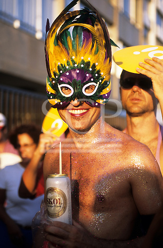 Rio de Janeiro, Brazil. Carnival; Banda de Ipanema, traditional gay street parade; man in mask drinking beer from a can with a straw.