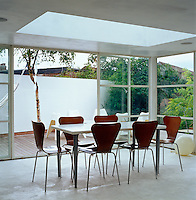 The doors of this glass-walled dining room open out on to the terrace
