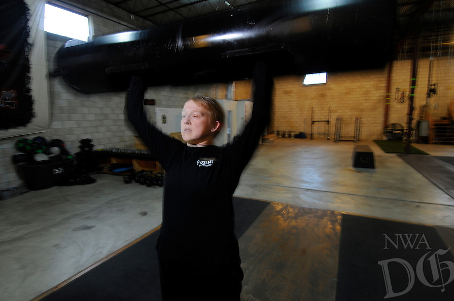 NWA Media/ J.T. Wampler - Syard Evans hoists a log while working out at CrossFit Fayetteville Dec. 27, 2014.