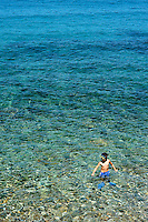 A boy in his flippers stands in the clear azure water of the Aegean Sea