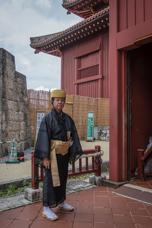 An attendant in traditional dress greets guests at Okinawa's restored Shur Castle grounds.