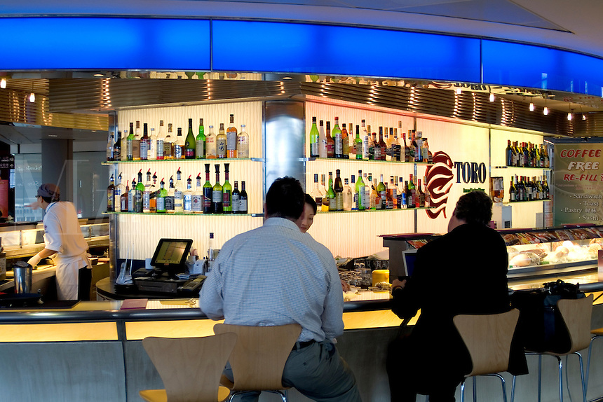Shiny new Hong Kong airport with stores and high tech items as travelers come and go in clean shiny environment terminal and this hi tech beautiful bar in airpor