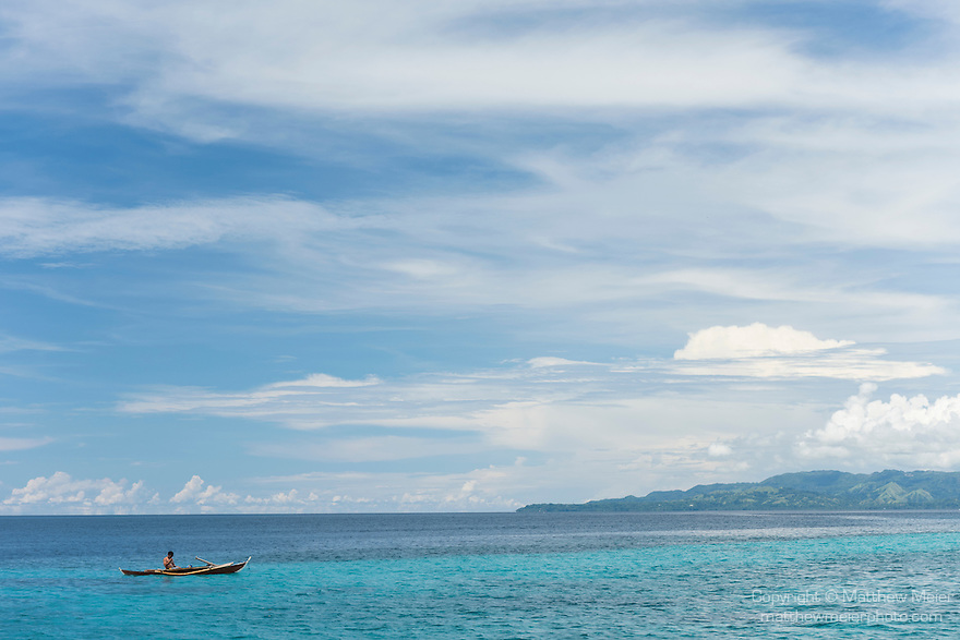 Anda, Bohol, Philippines; a local fisherman floats in his outrigger boat above shallow coral reefs along the shoreline visible beneath the water's surface in early morning light