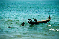 Local fishermen off the Atlantic Ocean coastline of Ghana, Africa; nets are used by these men to catch small quanities of fish which they eat themselves or sell in small markets; wooden, handmade boats are powered by hand paddles; catches often inc clud