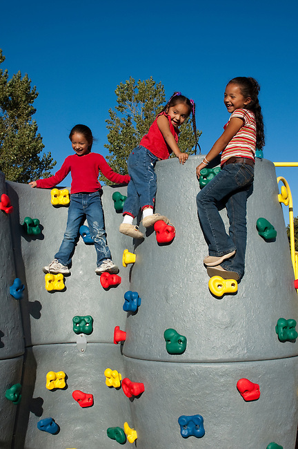 Three Native American elementary age girls climb up on wall outside at playground as an after school activity