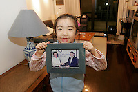 QS051128Shanghai026 20051128 SHANGHAI,CHINA: 7 year old Gao Xinyi shows a picture of her father Tango Gao (L) an advertising company executive, at her home in Shanghai, China 28 November 2005. With her parents often coming home late due to their work, Xinyi often spends her time away from school and other classes with her grand mother and a care taker, who came from a rural province. .* Pictures taken as a part of a photo story profiling a successful rising middle class family in Shanghai.*