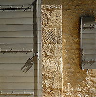 The shutters of a house in the Provence countryside are painted a subtle flat grey to contrast with the honey-coloured walls constructed from traditional stone