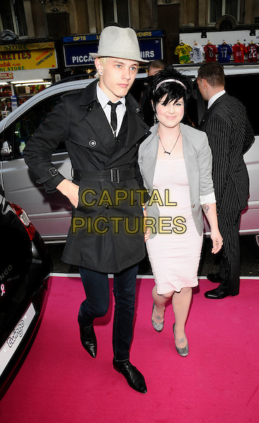 "LUKE HOWELL & KELLY OSBOURNE .""A Night Of Tease"" charity gala, Cafe De Paris, London, England..May 14th, 2008.full length pink dress grey gray jacket  hat black coat couple .CAP/CAN.©Can Nguyen/Capital Pictures."
