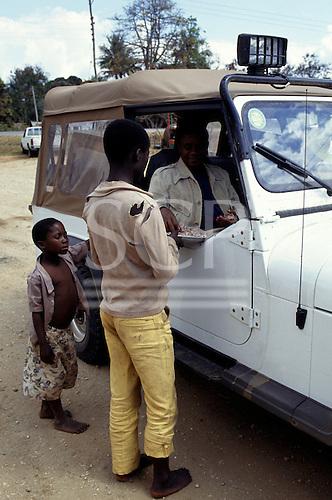 Mikumi, Tanzania. Local children selling peanuts to tourist in a four wheel drive jeep.