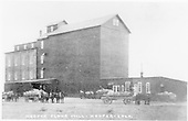 Hooper Flour Mill at Hooper on the D&amp;RG.  Five mule-drawn wagons with sacked grain are waiting to unload.<br /> D&amp;RG  Hooper, CO