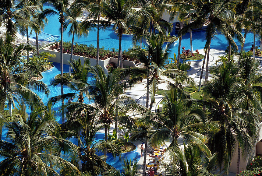 Pool partially obscured by palm trees at Regina Hotel. Puerto Vallarta, Mexico.
